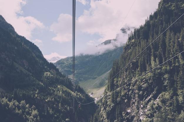 Сцены гор крупного плана, канатная дорога к мосту trift в национальном парке швейцарии, европе. летний пейзаж, солнечная погода, пасмурное небо и солнечный день