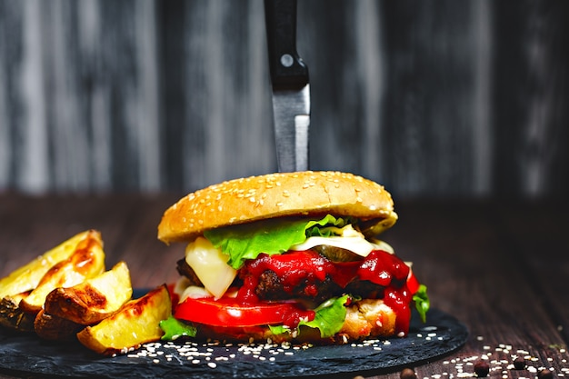 Closeup of mouth watering, delicious homemade burgers with a kni