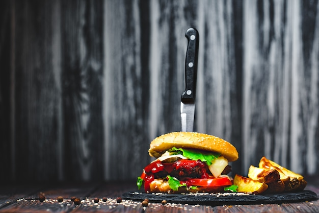 Closeup of mouth-watering, delicious homemade burgers with a knife stuck on stone board. dark