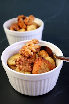 Closeup mouthwatering banana walnut bread pudding in a white bowl on black table