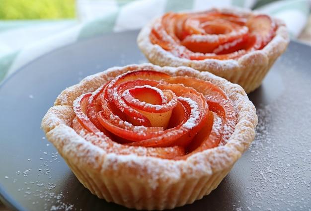 Аппетитные мини-тарталетки с яблоками и розами крупным планом на черной тарелке