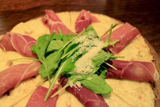 Closeup of mouthwatering prosciutto arugula cheesy pizza on wooden breadboard