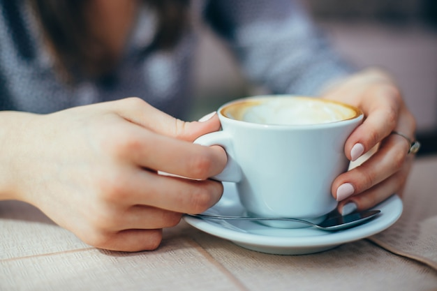 Closeup of mug with coffee in hands of woman.