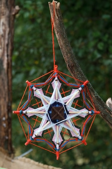 Closeup of a multicolored handwoven macrame dreamcatcher hanging on a branch in the park