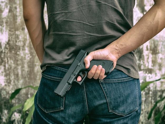 Closeup murder hidden gun behind his back