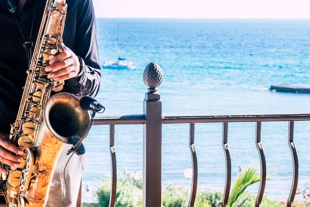 Closeup of music artist saxophonist  touching his instrument in the restaurant or bar with the beach or the sea or ocean