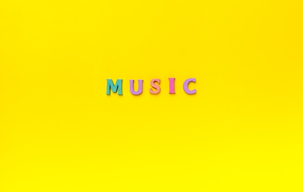 Closeup to a music lettering word over a yellow background. music lover concept