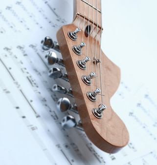 Closeup of music sheets and black-and-white electric guitar.isolated on a white background.photo with copy space.