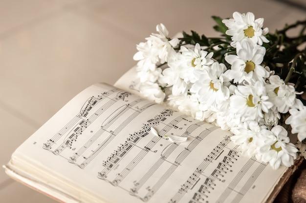 Primo piano di note musicali e un mazzo di fiori