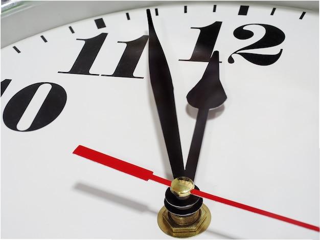 Крупным планом игла аналоговых часов белый фон арабский номер