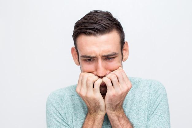 Closeup of nervous young man biting nails