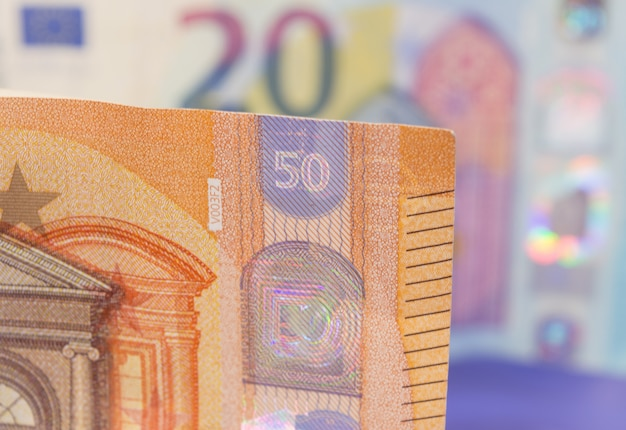 Closeup of new banknote of fifty euros with another twenty bill, out of focus in the background.
