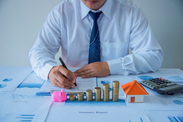 Closeup of new homeowner signing a contract of house sale or mortgage papers with a wooden toy house