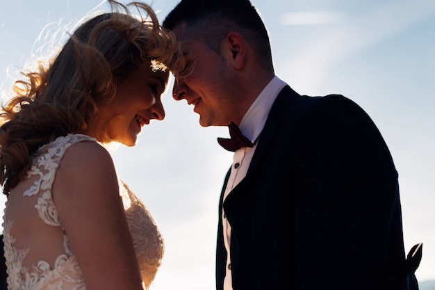 Closeup of newlyweds closed their eyes and hold their hands on the sky background smile