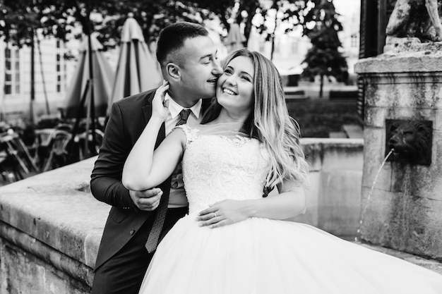 Closeup of newlyweds hugging and smiling at black and white photo.