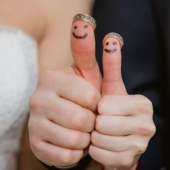 Closeup of newlyweds painted at fingers