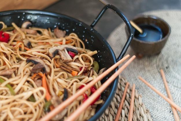 Лапша крупным планом с некоторыми овощами, такими как имбирь, лук, перец и грибы, заправленная соевым соусом. выборочный фокус