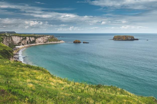 Береговая линия северной ирландии крупным планом, спокойная водная поверхность рядом с ирландской скалой, впечатляющая морская