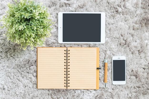 Макрофотография записная книжка, планшет, телефон и искусственное растение на фоне серого капет