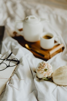 Closeup of a notebook, a cup of coffee, and white squashes in bed