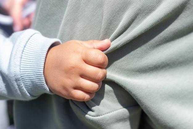 彼の母親の服を持っている赤ちゃんの手のクローズアップ