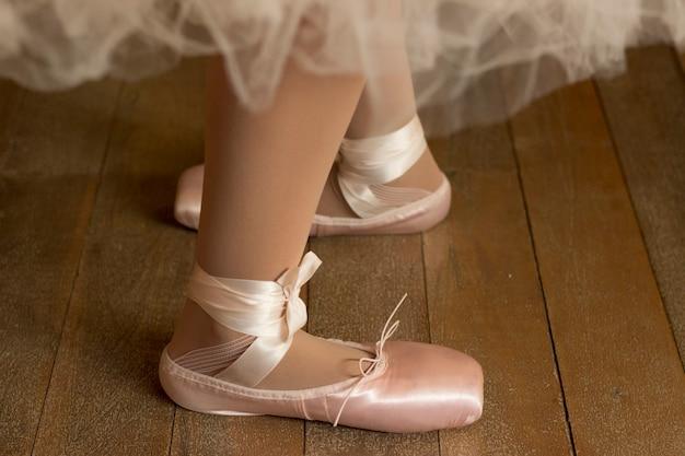 Крупным планом ноги балерины в пуантах на деревянном полу