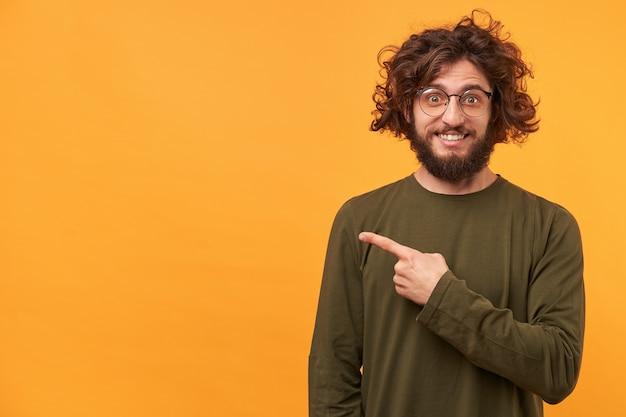 Крупным планом бородатый молодой парень выглядит довольным и удивленным, указывая указательным пальцем в сторону