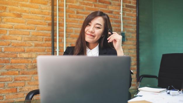 Крупный план красивой азиатской коммерсантки используя и работая на портативном компьютере в офисе