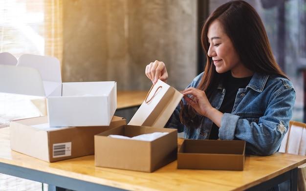 美しいアジアの女性のクローズアップを開くと配信とオンラインショッピングの概念のための自宅で買い物袋の中