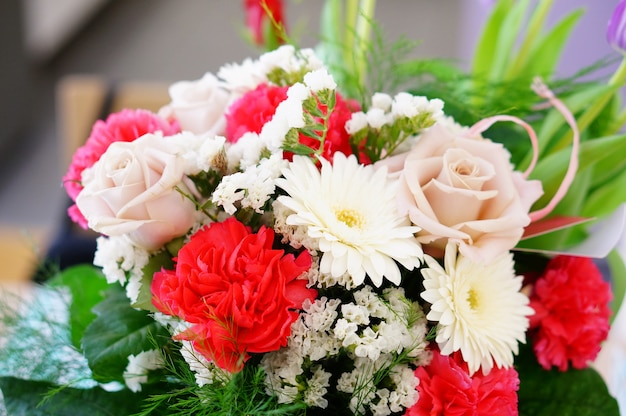 Крупным планом красивый букет цветов, состоящий из роз, статицы, гвоздики и ромашек