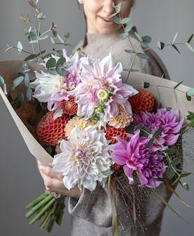 女性の手に菊と美しい花束のクローズアップ