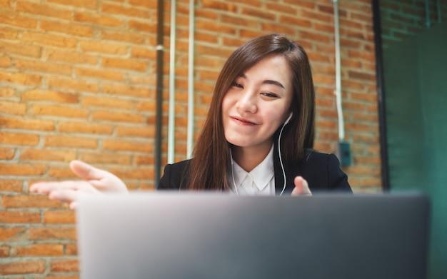 Макрофотография красивая деловая женщина, используя наушники для видеоконференции на портативном компьютере во время работы в интернете