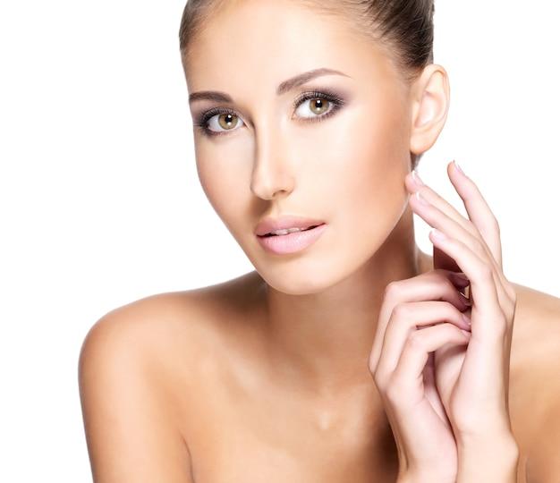 彼女の顔に優しく触れるきれいな新鮮な肌を持つ美しい若い女性のクローズアップ