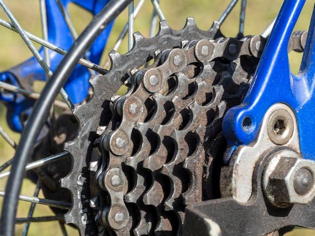 산악 자전거의 뒷바퀴에 있는 자전거 기어 메커니즘과 체인의 근접 촬영. 자전거에 기름과 먼지에 별이 있는 더러운 후면 카세트