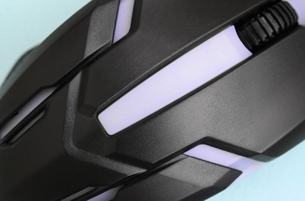 Макрофотография черной игровой оптической мыши на синем фоне