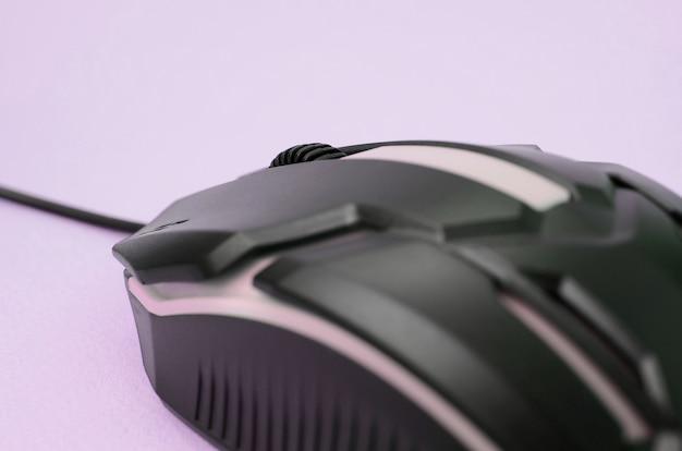Крупным планом черная игровая оптическая мышь на розовом