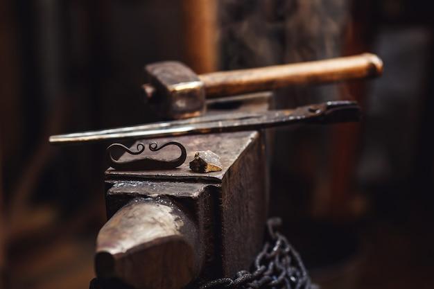 Крупный план кузнечной наковальни с молотом, клещами, firesteel и кремнем.