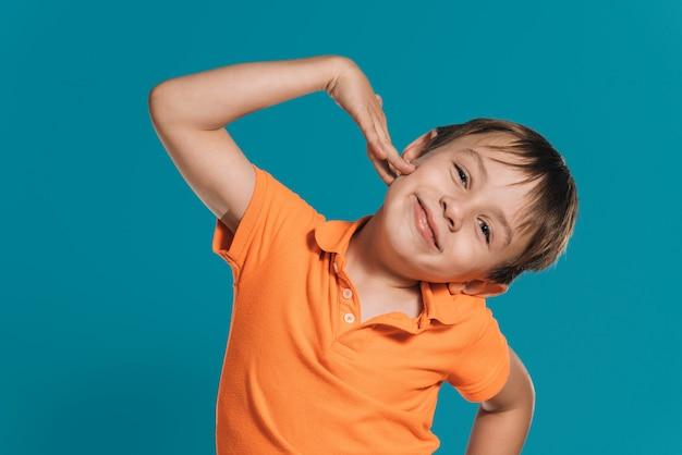 青い背景の上の彼の顔に笑顔でポーズをとってオレンジ色のtシャツを着た金髪の少年のクローズアップ