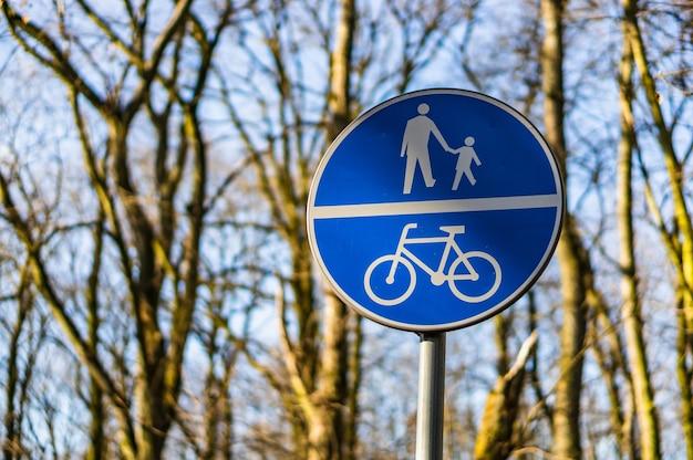 흐린 배경으로 햇빛 아래 사람과 자전거를위한 파란색 도로 표지판의 근접 촬영