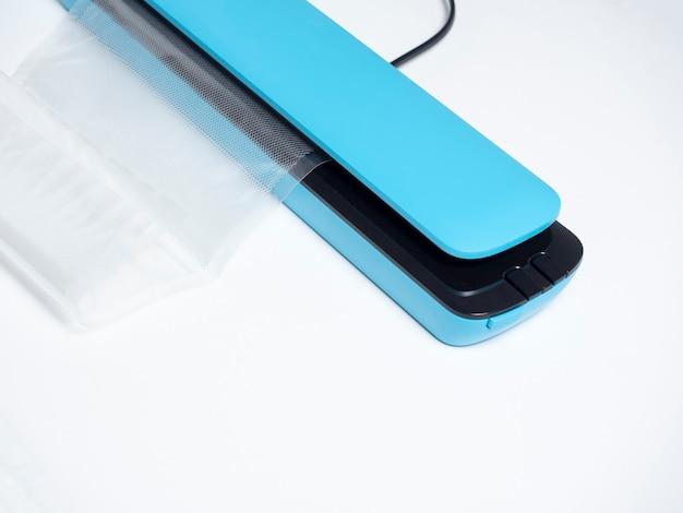 밝은 파란색 배경에 격리된 파란색 진공 포장기의 클로즈업 패키지가 삽입됩니다.