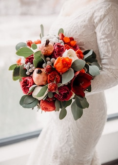 赤い花のブライダルブーケを持って、エレガントなウェディングドレスを着ている花嫁のクローズアップ
