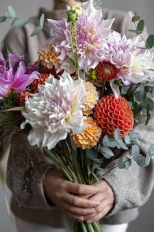 女性の手に菊と明るいお祭りの花束のクローズアップ