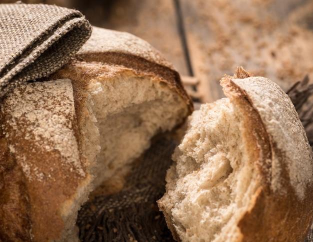 Крупный план сломанной буханки хлеба на тканевой салфетке