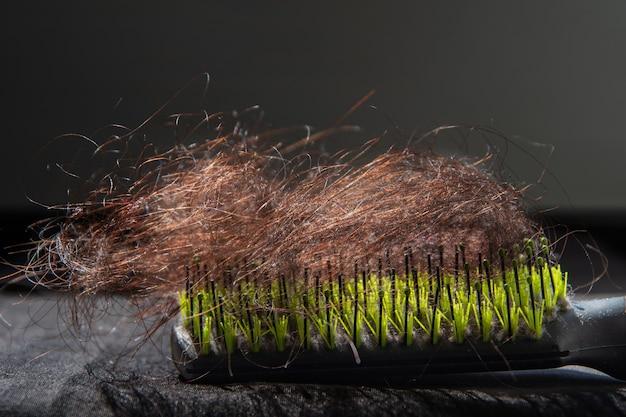 Крупный план пучка изогнутых коричневых человеческих волос, падающих с женщины, лежащей на черно-зеленой расческе.