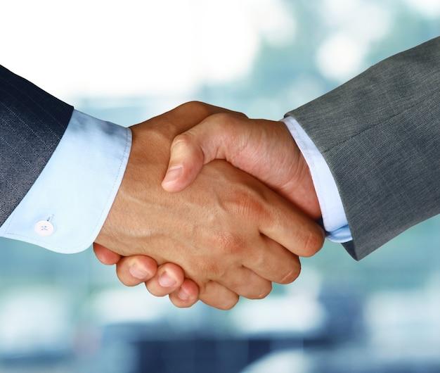 2人の同僚間のビジネス握手のクローズアップ