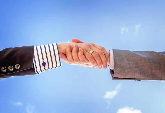青空の背景上のビジネス握手のクローズアップ