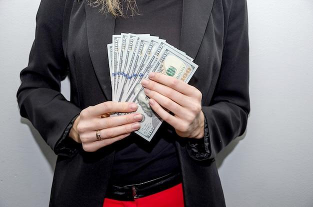 彼女の手にドルを持つビジネスウーマンのクローズアップ