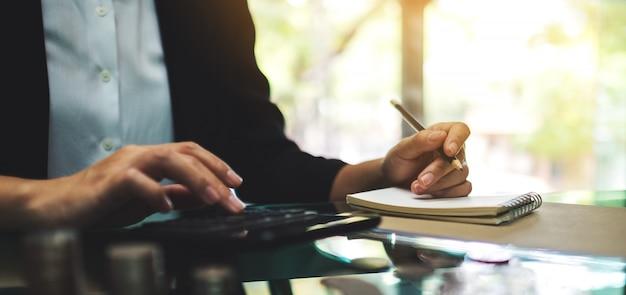 Макрофотография деловой женщины, работы, расчета и записи на ноутбуке в офисе