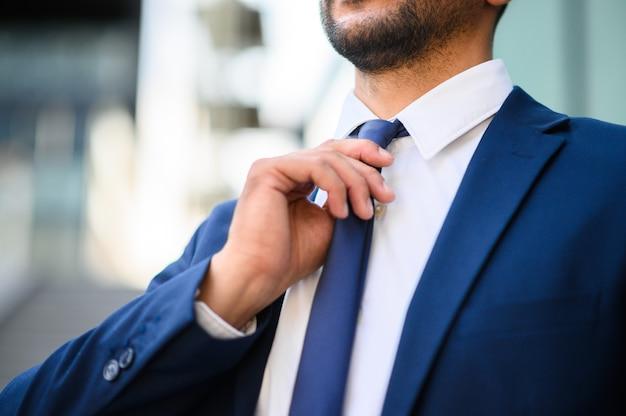 彼のネクタイを調整するビジネスマンのクローズアップ