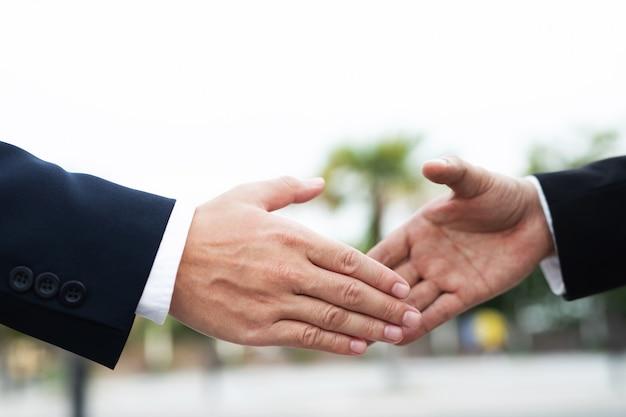 ビジネスマンのクローズアップ手2人の同僚の間で投資家を振るok、ビジネスに成功手をつないで。